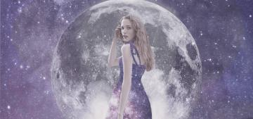 A young woman with blonde hair dressed in a purple dress stood in from of the moon and the expanse of space